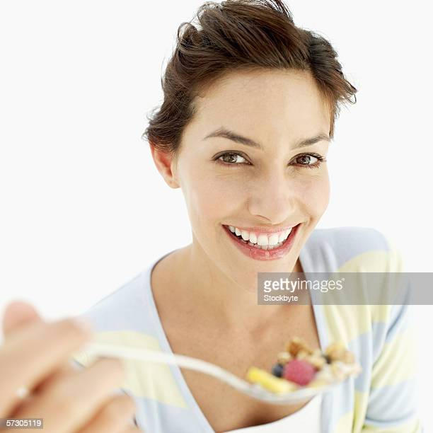 Close-up of a young woman holding a spoonful of cereal