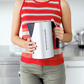Close-up of a young woman holding an electric kettle