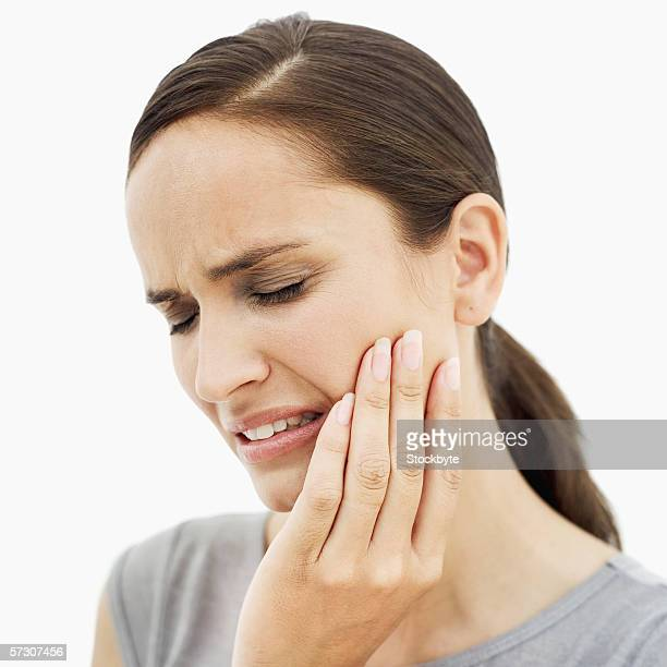 Close-up of a young woman holding the side of her face in pain