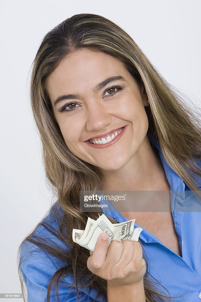 Close-up of a young woman holding US paper currency : Stock Photo