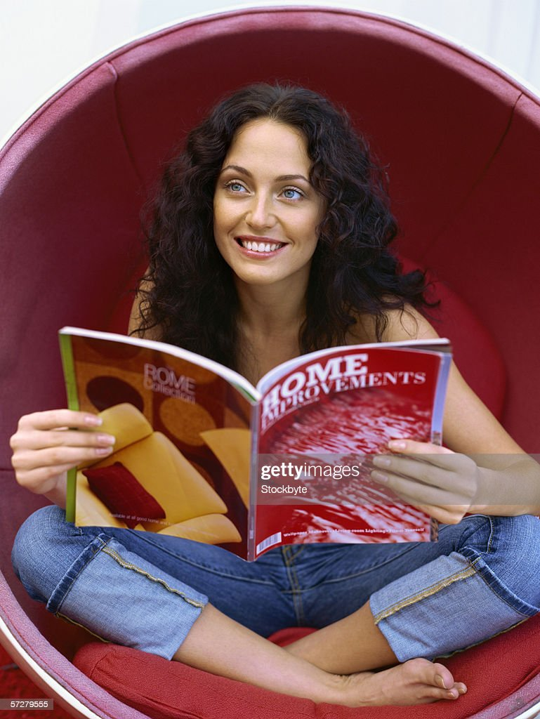 Close-up of a young woman in a funky armchair : Stock Photo