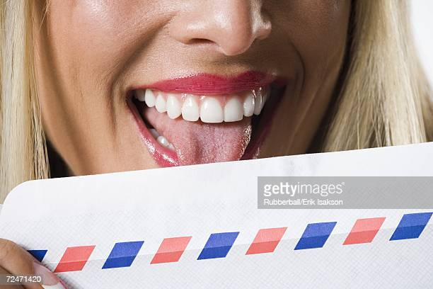 Close-up of a young woman licking an envelope
