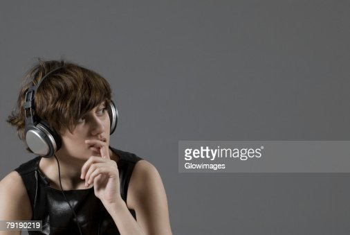 Close-up of a young woman listening to music and thinking : Foto de stock
