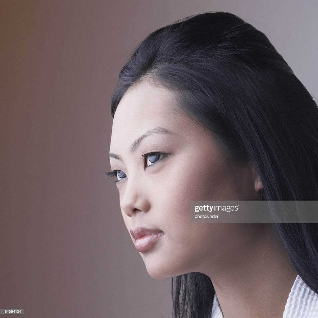 Close-up of a young woman looking away : Stock Photo