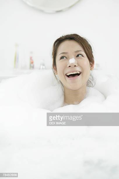 Close-up of a young woman looking cheerful in a bathtub