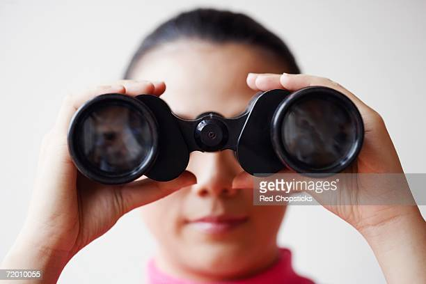 Close-up of a young woman looking through a pair of binoculars