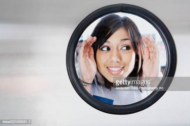 Close-up of a young woman looking through a window