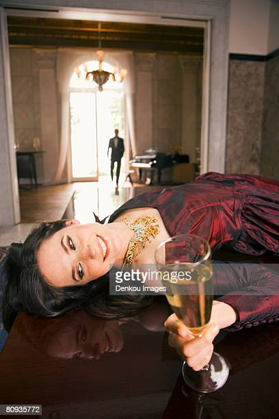 Close-up of a young woman lying on a table and holding a champagne flute