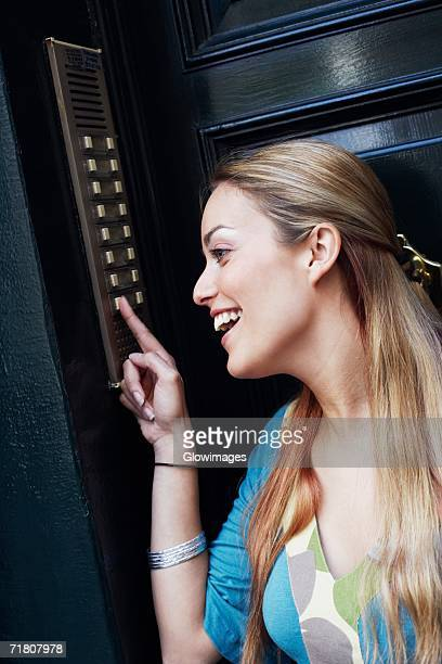 Close-up of a young woman pressing a doorbell
