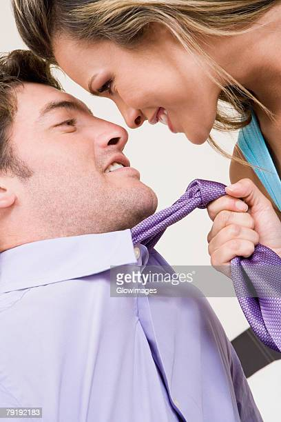 Close-up of a young woman pulling a mid adult man towards her with his tie