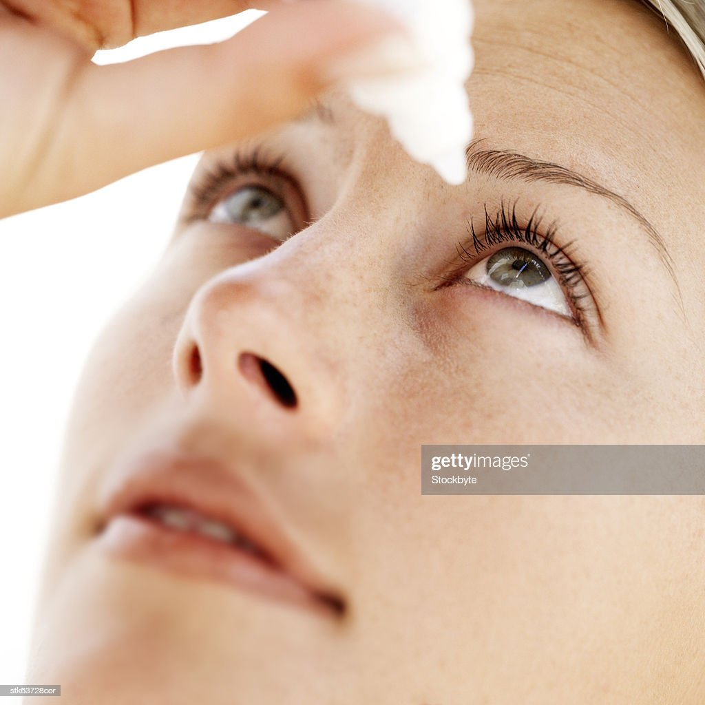 close-up of a young woman putting eye drops in eye : Stock Photo
