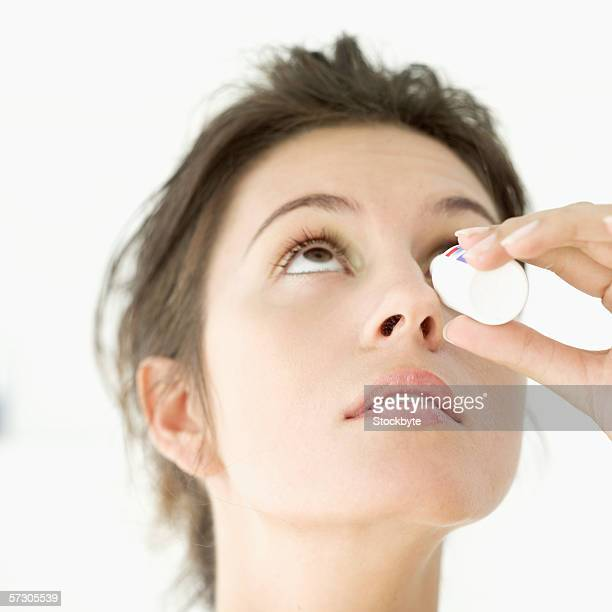 Close-up of a young woman putting eye drops in her eyes