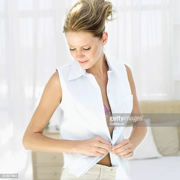 Close-up of a young woman putting on a sleeveless shirt