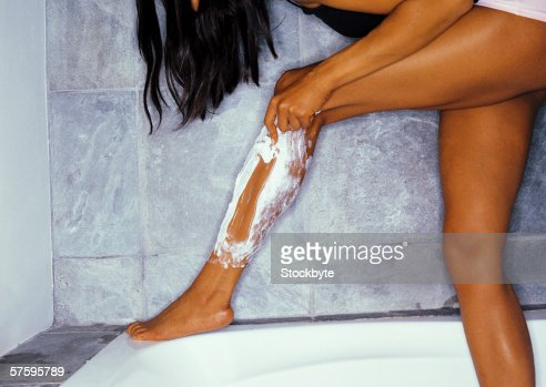 Close-up of a young woman shaving her leg : Stock Photo