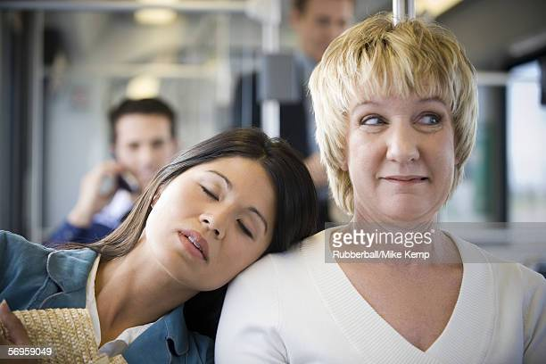Close-up of a young woman sleeping on a mature woman's shoulder