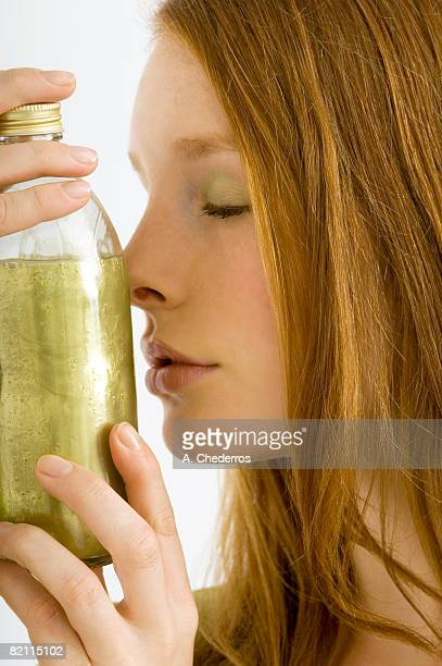 Close-up of a young woman smelling a bottle of aromatherapy oil