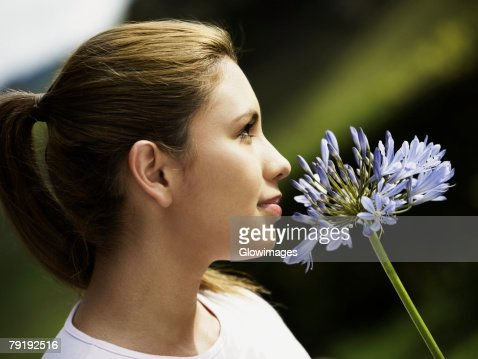 Close-up of a young woman smelling a flower and thinking : Foto de stock
