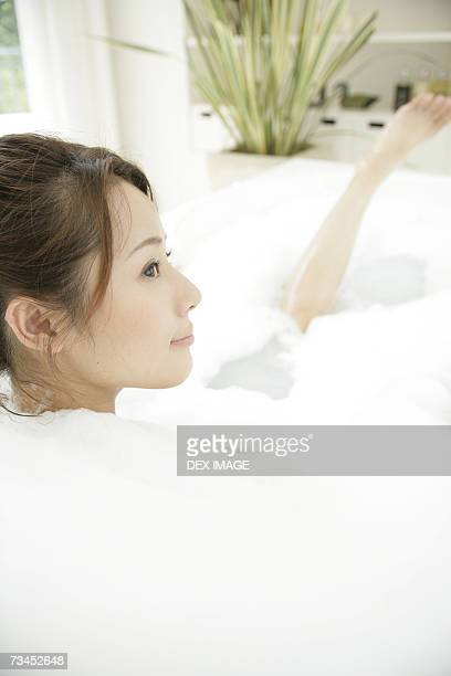Close-up of a young woman soaking in a bubble bath