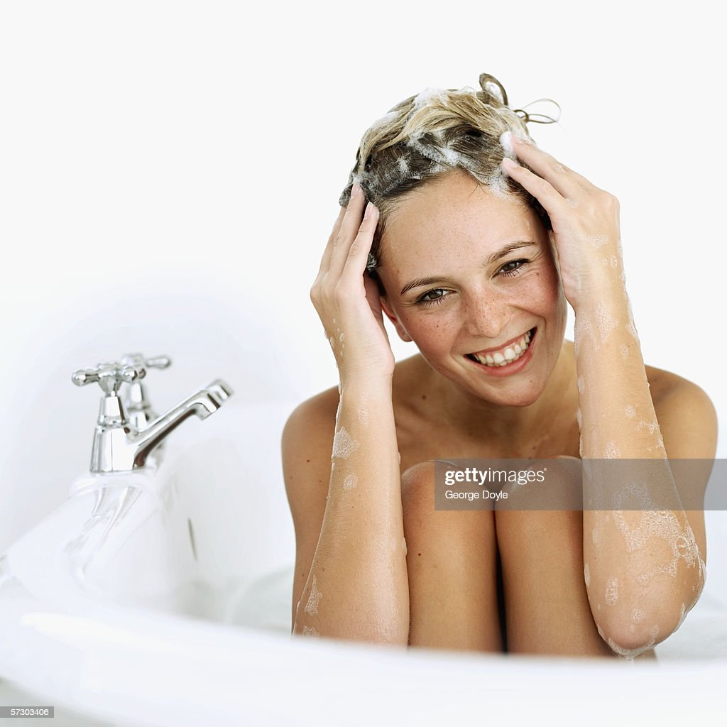 Close-up of a young woman soaping her hair in a bathtub : Stock Photo