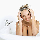 Close-up of a young woman soaping her hair in a bathtub