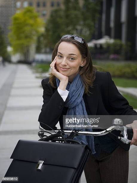 Close-up of a young woman standing with a bicycle