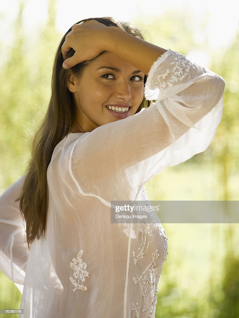 Close-up of a young woman standing with her hand in her hair : Stock Photo