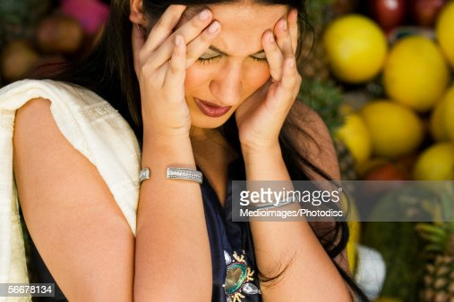 Close-up of a young woman standing with her hands on her forehead : Stock Photo