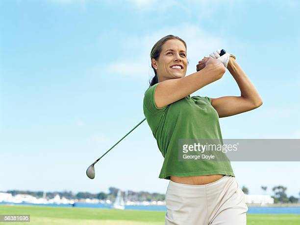 Close-up of a young woman swinging a golf club