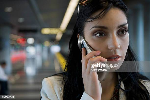 Close-up of a young woman talking on a mobile phone at a subway station