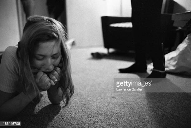 Closeup of a young woman under the influence of LSD as she lies on the carpet of an apartment her chin in her hands Los Angeles California 1966