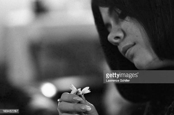 Closeup of a young woman under the influence of LSD examines a daisy in her hand Los Angeles California 1966