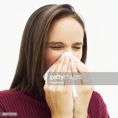 Closeup Of A Young Woman Wiping Her Nose With A Tissue ...