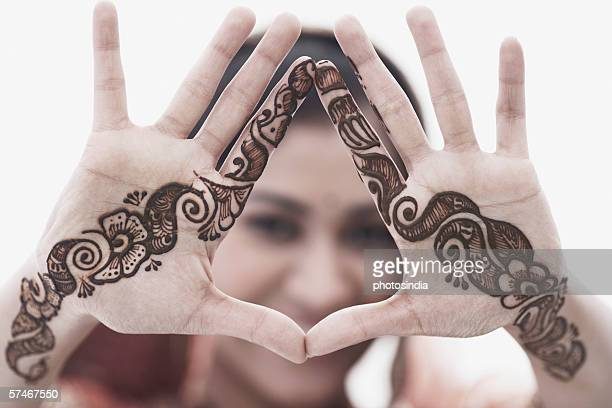 Close-up of a young woman with henna tattoo's on her hands
