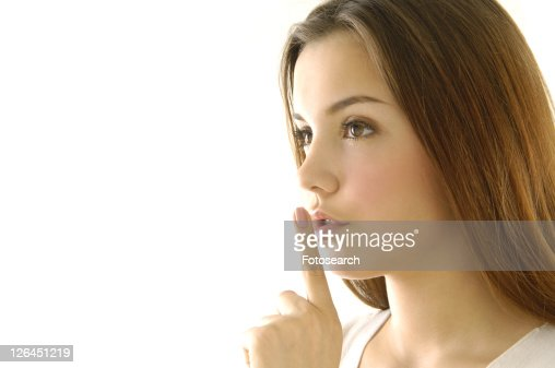 Close-up of a young woman with her finger on her lips : Stock Photo
