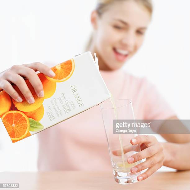 Close-up of a young woman's hands pouring juice from a carton into a glass (blurred)