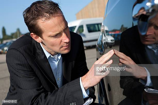 Close-up of accessor examining car damage for insurance