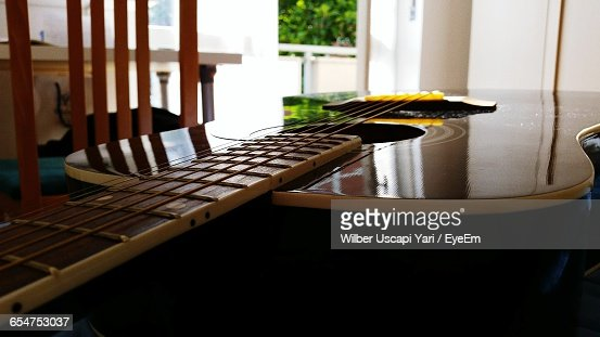 Close-Up Of Acoustic Guitar On Table At Home