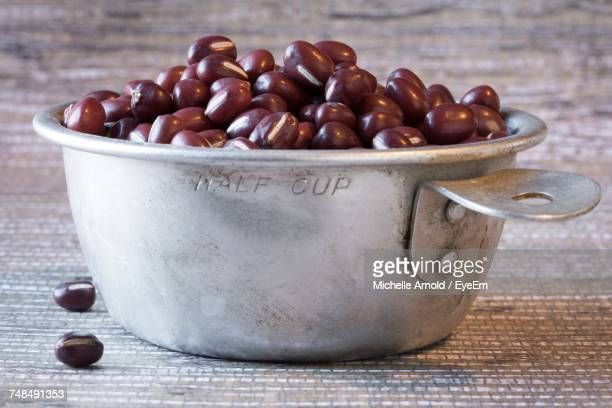 Close-Up Of Adzuki Beans In Measuring Cup On Table