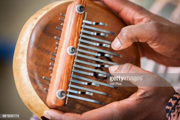 Closeup of African American hands playing a lamellophone musical instrument
