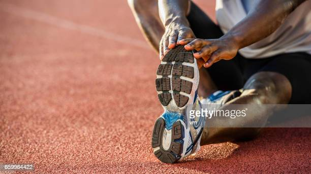 Close-up of African-American athlete stretching his leg