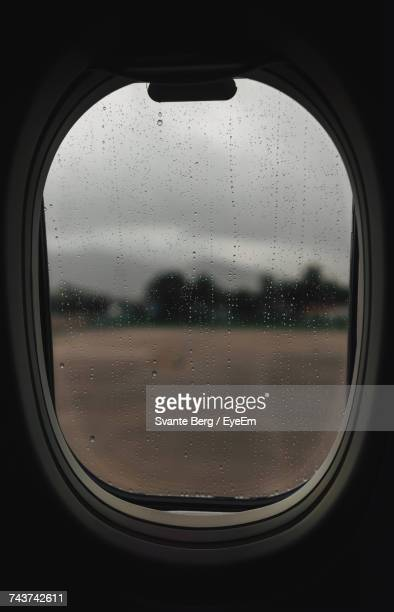 Close-Up Of Airplane Window During Rainy Season
