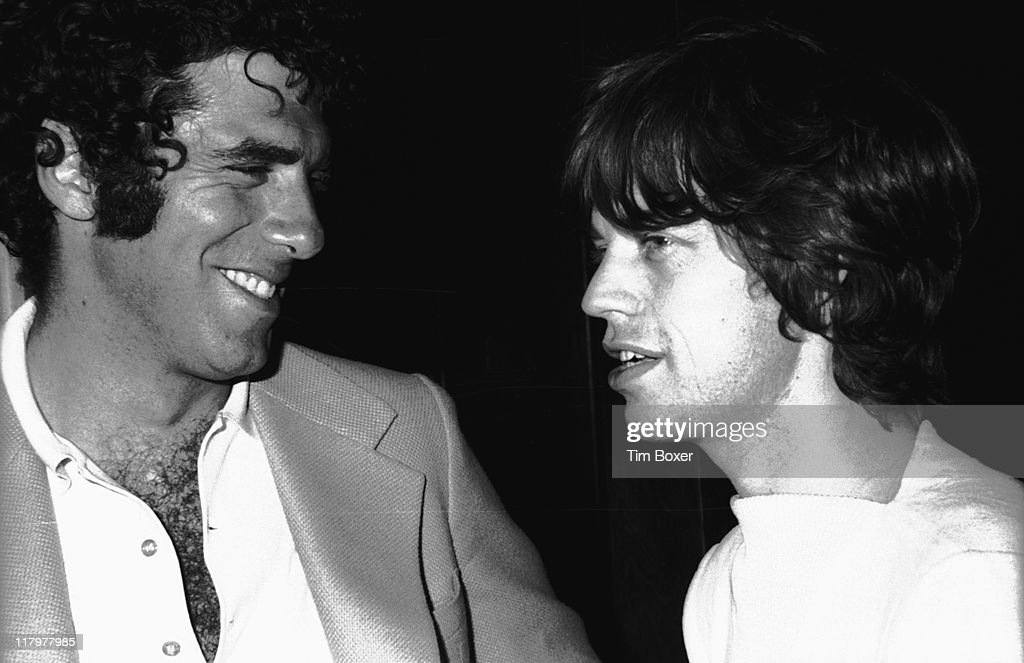 Closeup of American actor Elliott Gould and British singer Mick Jagger as they attend a party at Le Club New York New York July 1974