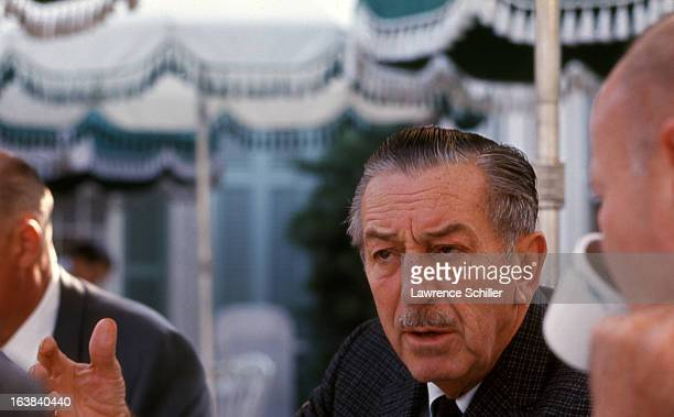 Closeup of American businessman animator and director Walt Disney as he speaks to unidentified men at an outdoor cafe at the Disneyland theme park...