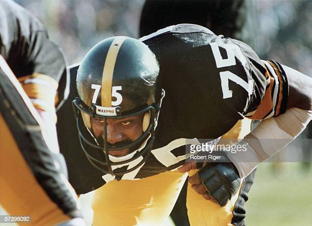 Closeup of American football player 'Mean Joe' Greene of the Pittsburgh Steelers as he crouches on the field eyeing his opponant 1970s