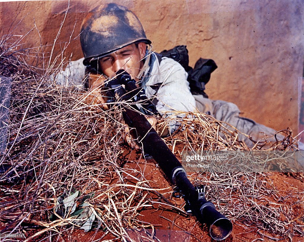 Close-up of American soldier Private Charles P. Coopers as he peers through the telescopic sight of his rifle, early 1940s. The gun appears to be a varient of the Standard M1 Garand, augmented with an M84 sight and an M2 flash-hider, which suggest that it is either an M1C or M1D sniper rifle.