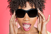 Close-up of an African American woman wearing sunglasses over colored background