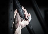 Right hand of a gym male athlete gripping an iron chalky gymnastic bar.