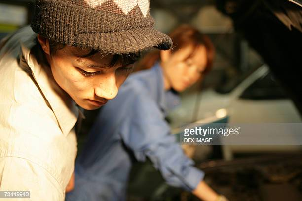Close-up of an auto mechanic looking down with a female mechanic in the background