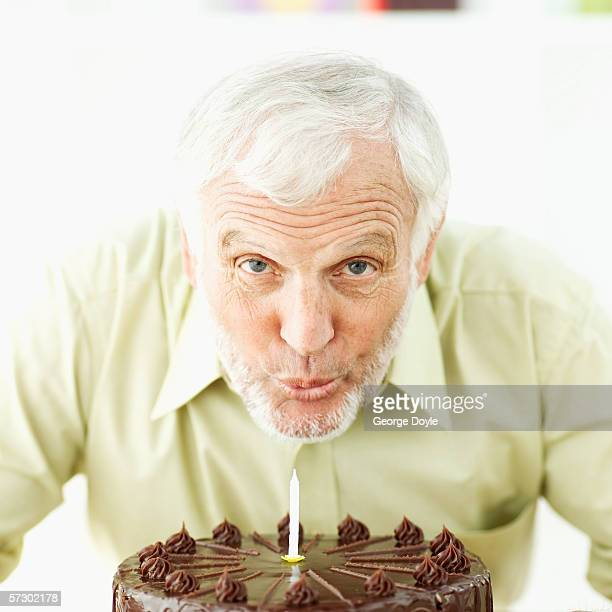 Close-up of an elderly man blowing candles out on birthday cake