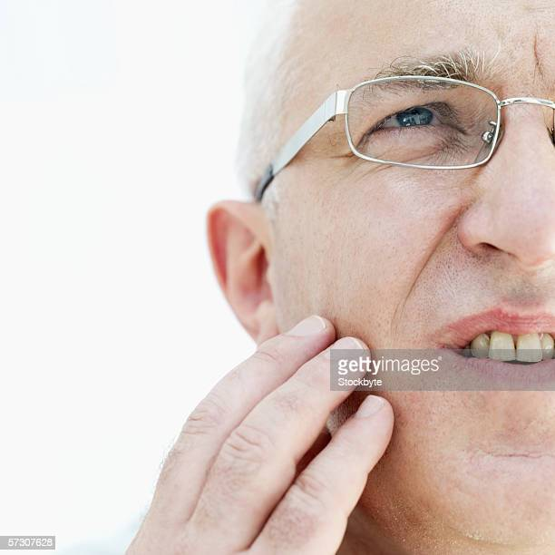 Close-up of an elderly man touching his cheek in pain